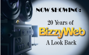"""camera pointing at a screen with text overlaid that says """"NOW SHOWING: 20 Years of BizzyWeb, A Look Back"""""""