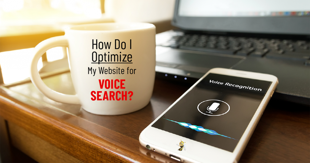 "a coffee mug next to a phone with voice recognition software activated. text overlaid says ""how do i optimize my website for voice search?"""