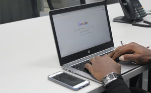 hands typing on a laptop with Google's homepage on the screen
