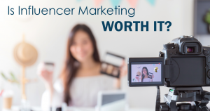 """a woman holding makeup in front of a filming camera, with text overlaid that says """"is influencer marketing worth it?"""""""